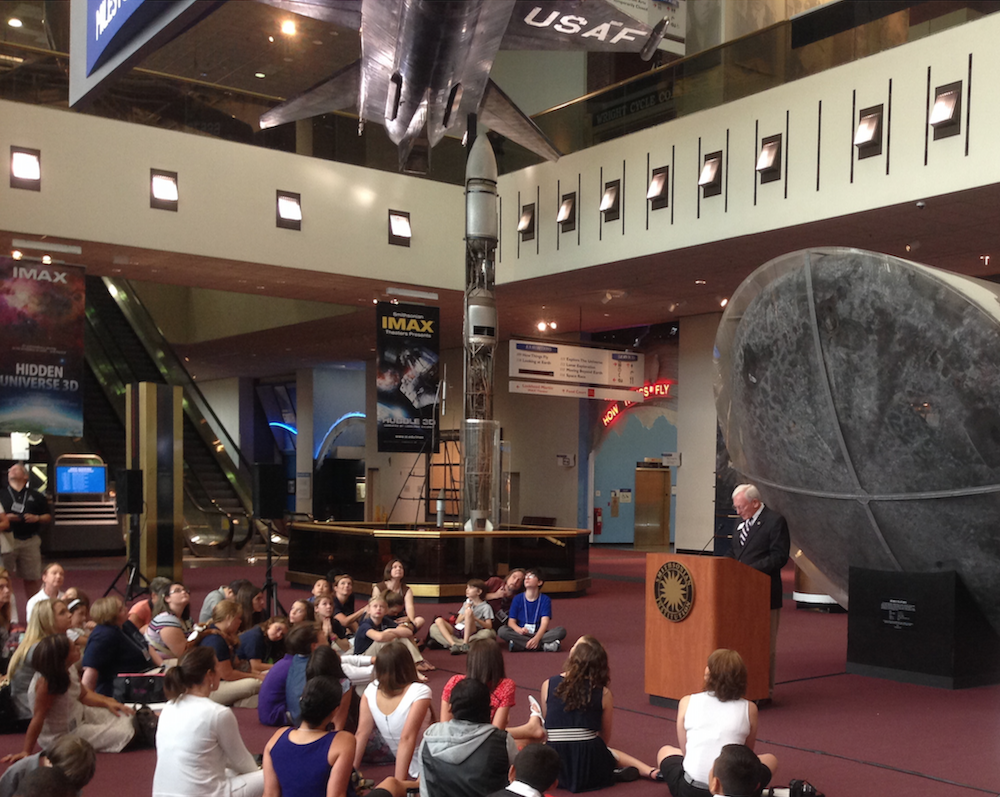"General John R. ""Jack"" Dailey, Director of the Smithsonian National Air and Space Museum, a SSEP National Partner organization, addresses 200 hundred delegates on Day 2 of the 2014 SSEP National Conference, July 3 ,2014. Behind him is Columbia, the Apollo 11 Command Module that safely returned Neil Armstrong, Edwin ""Buzz"" Aldrin, and Michael Collins from the Moon, and above him an X-15, the first winged aircraft to travel 4, 5 and 6 times the speed of sound. General Dailey has said that SSEP ""may be the most important development for the future of the U.S. space program"" (read about it). CLICK TO ZOOM"