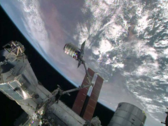 "The International Space Station's robotic arm, Canadarm2, grapples the Orbital Sciences' Cygnus cargo craft named ""Janice Voss"" on July 16, 2014. Image Credit: NASA TV Read more: http://www.universetoday.com/113281/cygnus-commercial-resupply-ship-berths-to-space-station-on-45th-apollo-11-anniversary/#ixzz37jG6nhZb"