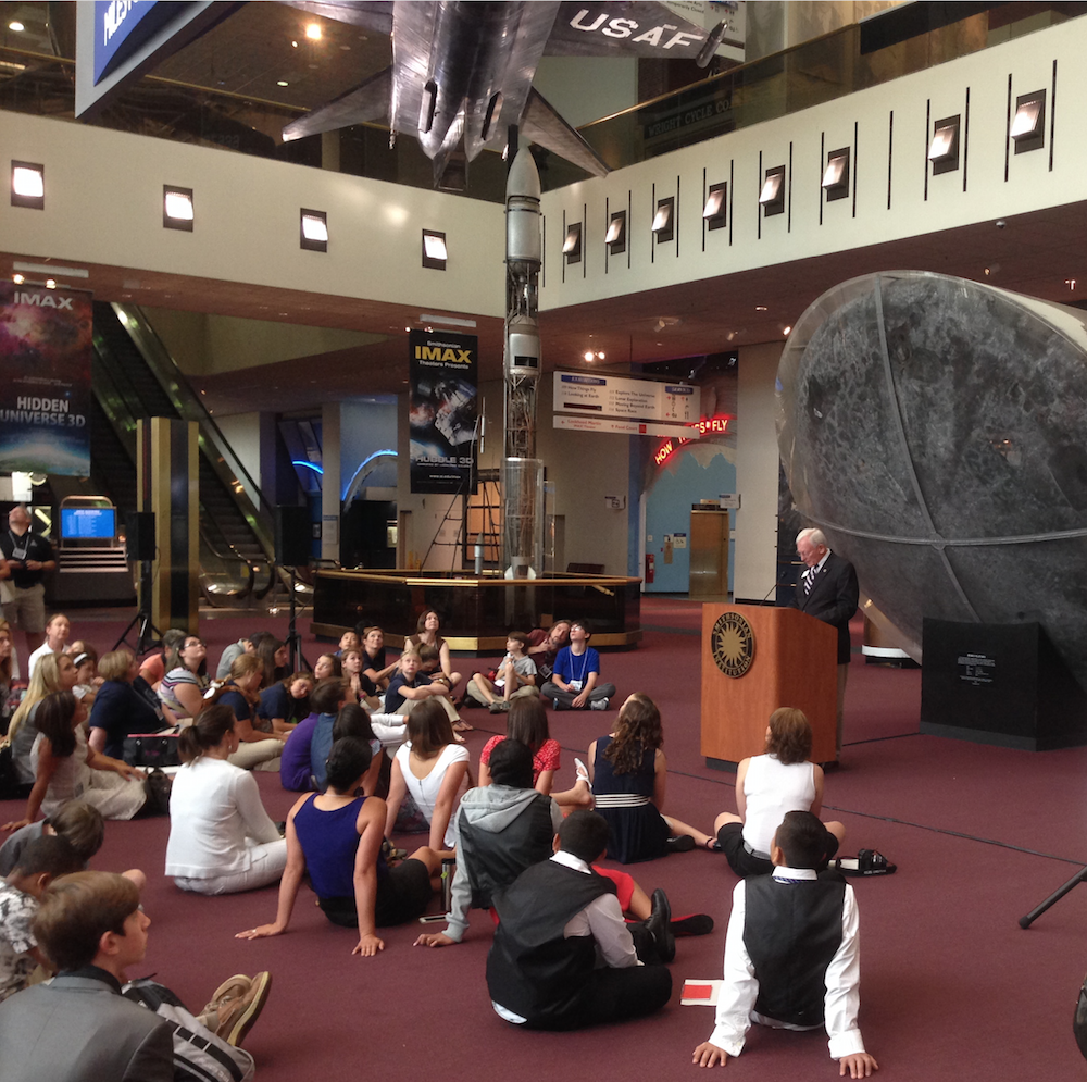 """General John R. """"Jack"""" Dailey, Director of the Smithsonian National Air and Space Museum, a SSEP National Partner organization, addresses 200 delegates on Day 2 of the 2014 SSEP National Conference, July 3 ,2014. Behind him is Columbia, the Apollo 11 Command Module that safely returned Neil Armstrong, Edwin """"Buzz"""" Aldrin, and Michael Collins from the Moon, and above him an X-15, the first winged aircraft to travel 4, 5 and 6 times the speed of sound. General Dailey has said that SSEP """"may be the most important development for the future of the U.S. space program"""" (read about it). CLICK TO ZOOM"""