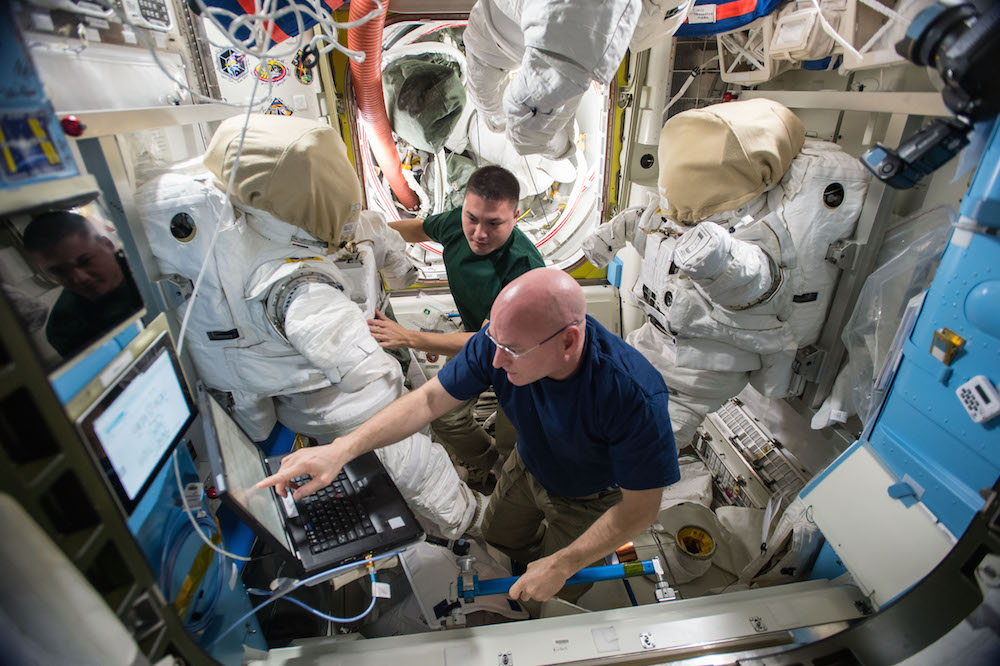 Expedition 45 commander Scott Kelly and flight engineer Kjell Lindgren prepare their extravehicular mobility unit spacesuits and tools in the Quest airlock. Kelly and Lindgren will use the spacesuits for two upcoming spacewalks outside the International Space Station on Oct. 28 and Nov. 6, 2015. Credits: NASA